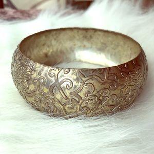 Metal bangle with floral/vine.